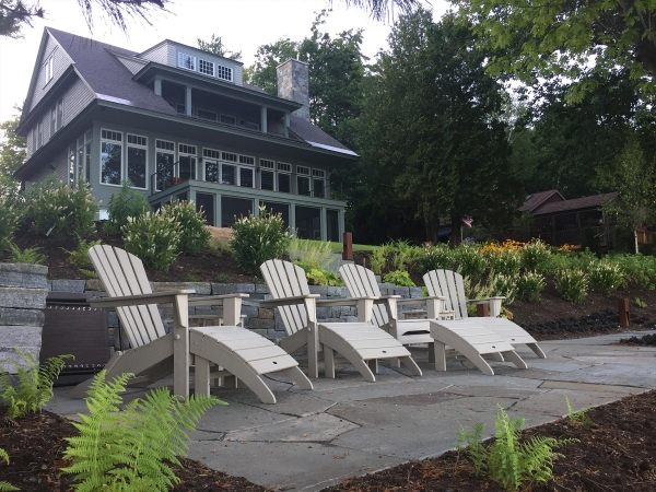 Adirondack chairs on stone patio in front of house