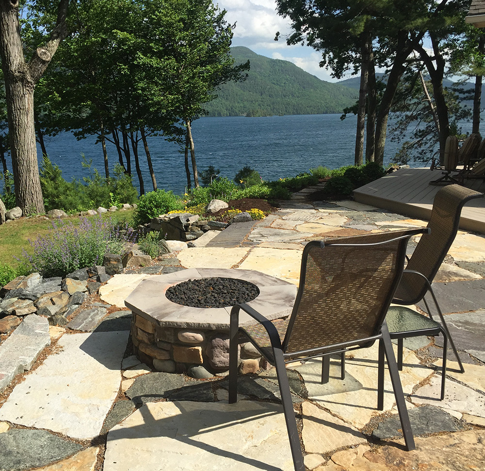 Stone patio with firepit overlooking lake George and Adirondack Mountains