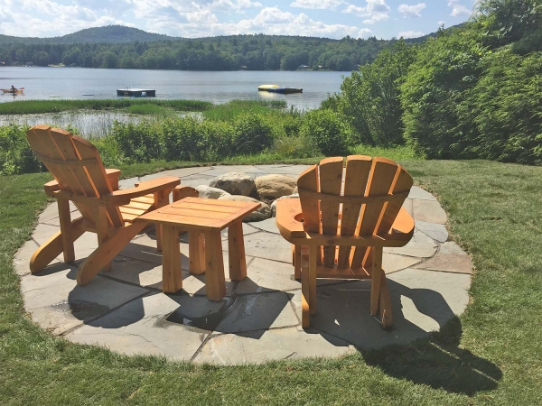 2 adirondack chairs looking out over lake on small patio