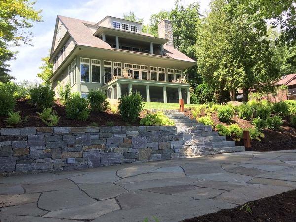 Stone patio and stone wall with stairs leading to house