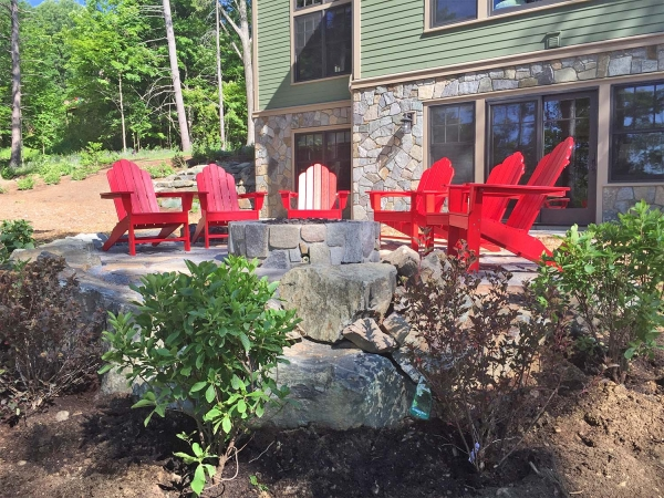 Red adirondack chairs in front of lake home