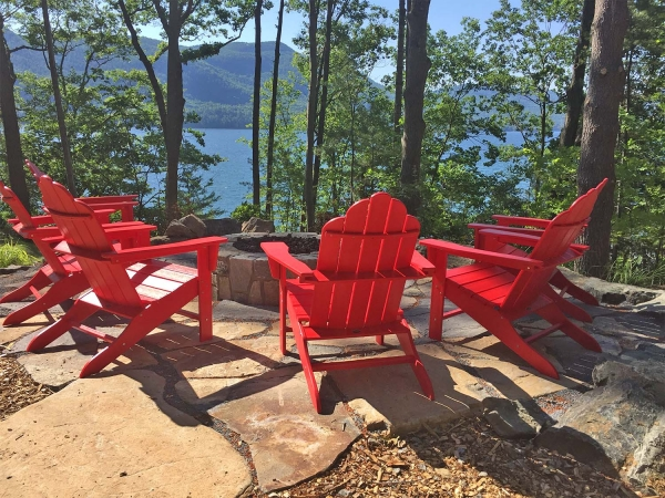 Red adirondack chairs overlooking lake george