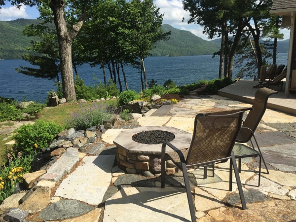 chairs around stone firepit overlooking lake george