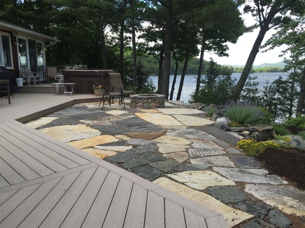 stone patio next to deck with firepit