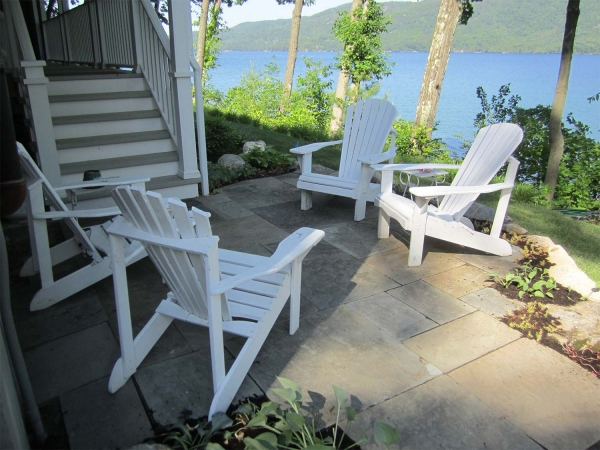 adirondack chairs on stone patio next to lake