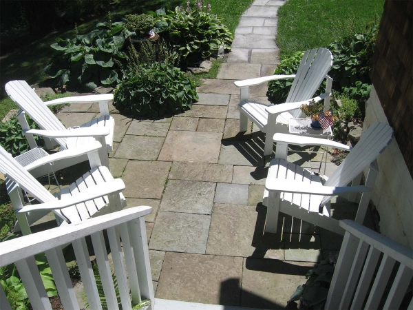 white Adirondack chairs on stone patio