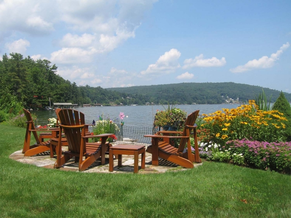 Brown Adirondack chairs overlooking lake