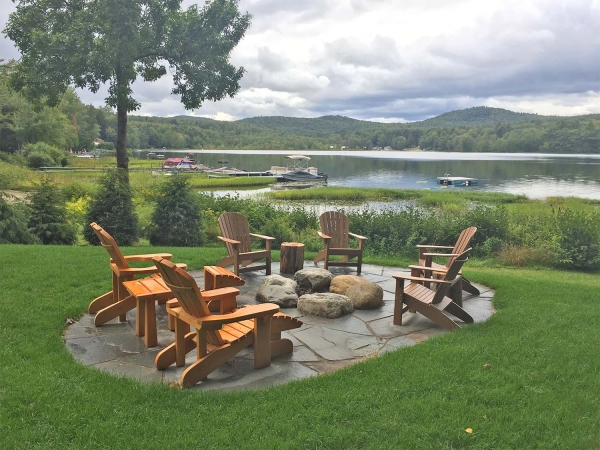 Adirondack chairs around stone firepit overlooking lake
