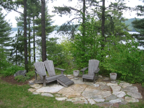 Adirondack chairs on stone patio overlooking lake