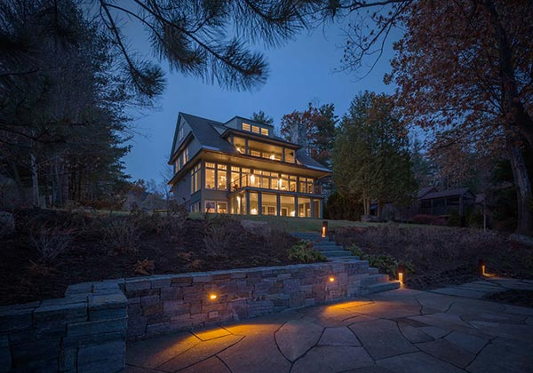 Large home lit at night with stone patio and wall